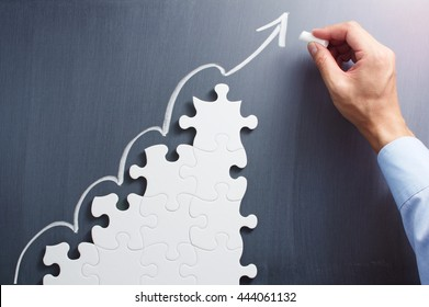 Business planning. Concept image of developing growth strategy. Steps shaped jigsaw puzzle. Drawing arrow on blackboard.