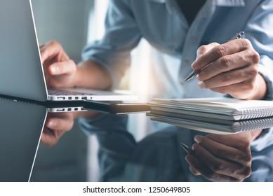 Geschäftsplanung, E-Learning-Konzept. Geschäftsmann, der auf Notebooks schreibt und in einem modernen Büro am Laptop arbeitet. Mann, der Online-Kurs über Laptop und Vortrag auf Notizblock.