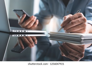Business planning, Elearning concept. Casual business man writing on notebook and working on laptop computer in office. Man using mobile phone, studying online course via laptop and lecture on notepad