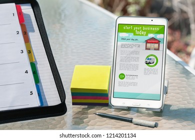 Business planning in outdoor setting with notes, scheduling folder and mobile phone with home based business information to get started today.