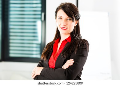 Business - Portrait of a businesswoman in business clothes in an Office, she smiles at the camera