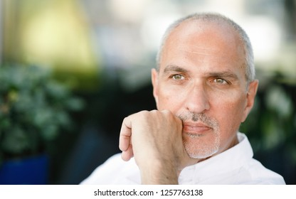 Business portrait of a calm and confident mature tanned European man with a bald head, looking at the street sitting in a summer cafe. Man in city. Lifestyle. Summertime. Copy space. Business life