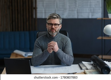 Business portrait of handsome bearded man wearing eyeglasses sitting at workplace. Confident businessman became successful. Interior designer working in office with laptop. Business concept.