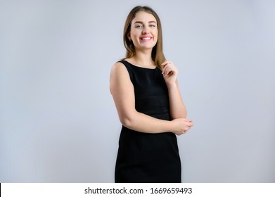 Business portrait on a white background sympathetic Caucasian woman in a black dress with a smile