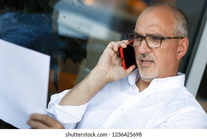 Business portrait of a pensive and energetic mature European man with glasses and a bald head talking on a smartphone with a lawyer and reading a contract while sitting in a cafe. Summer. Lifestyle