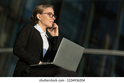 Business portrait of a stylish and happy young woman with blond hair and glasses, talking with a smile on a smartphone while working at a laptop against the windows of a skyscraper. Summer lifestyle