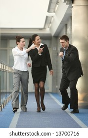 Business portrait of tree persons - young man and two women happy from success on modern office corridor
