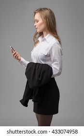 business portrait of a woman. on gray background. talking on the phone.
