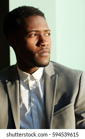 Business portrait of young handsome African-American man standing in sunlight against wall and looking away