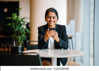 Business portrait of a young Indian Asian woman professional in a suit sitting at a desk in her office. She is smiling as she is looking at her smartphone.