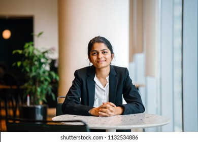 Business portrait of a young Indian Asian woman professional in a suit sitting at a desk in her office. She looks, happy, hopeful and confident about her future.