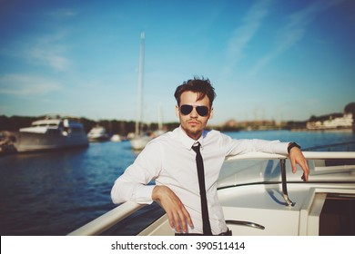 Business portrait of young man in suit with tie and sunglasses posing on a yacht and blue sea bay and sky background in a daylight sun