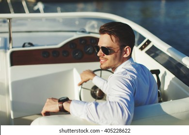 Business portrait of young smiling stylish man in suit and sunglasses driving yacht
