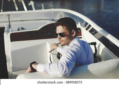 Business portrait of young stylish man in suit driving yacht