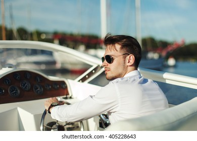Business portrait of young stylish man in suit and sunglasses driving luxury motorboat yacht