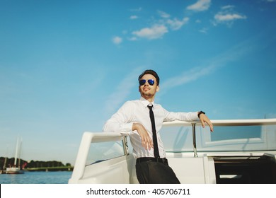Business portrait of young stylish smiling man in suit and sunglasses posing on a yacht on blue sky background