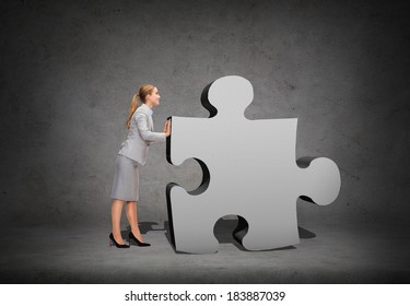 business, post and transportation concept - smiling businesswoman pushing big puzzle piece