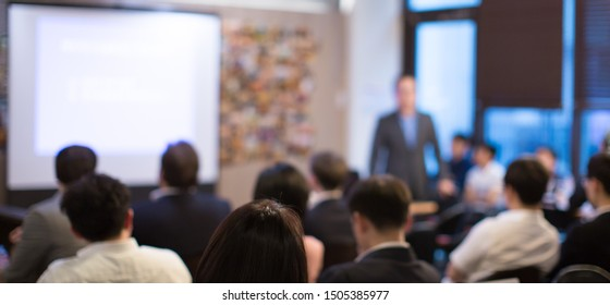 Business presentation being given by executive manager. Corporate seminar with expert speaker presenting to people. Presenter giving speech during lecture. Leadership training coach in workshop.