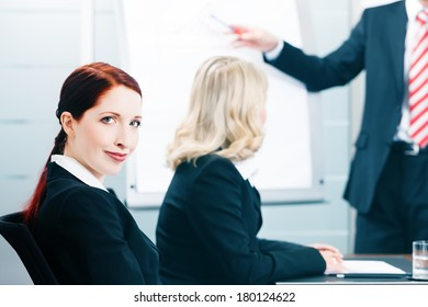 Business - presentation within a team, a colleague is standing on the flipchart