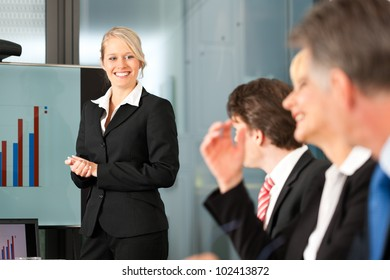 Business - presentation within a team, a female, colleague is standing on the flipchart