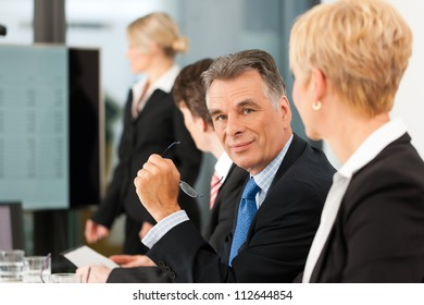 Business - presentation within a team, a female, colleague is standing on the flipchart, one man is looking into the camera