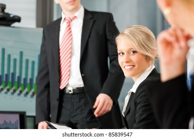 Business - presentation within a team; a male, colleague is standing on the flipchart