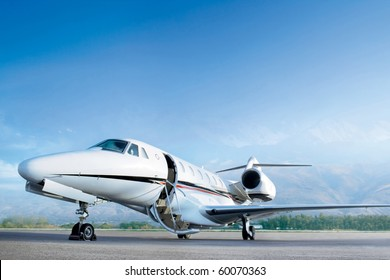 Business private jet airplane on airfield. Waiting a passenger with open door. Business and power concept.