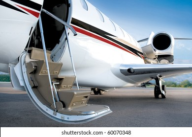 Business private jet with open stairs waiting for passenger, early morning, blue sky. Open door. Ready jet.