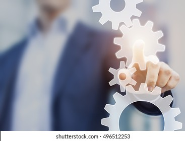 Business process automation and workflow improvement concept represented by a businessman touching a cogwheel connected with other gears