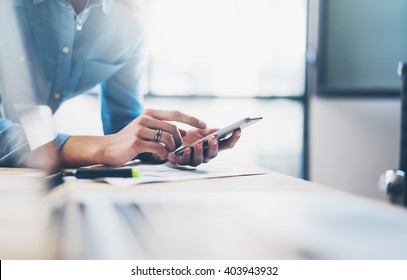 Business process photo. Account manager using mobile phone. Typing contemporary smartphone screen. Horizontal. Film effect. Blurred background