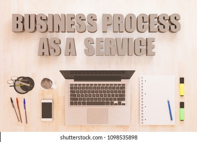 Business Process as a Service - text concept with notebook computer, smartphone, notebook and pens on wooden desktop. 3D render illustration.
