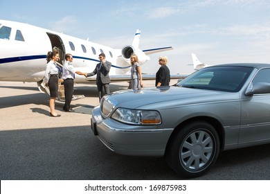 Business professional greeting airhostess and pilot near private jet and limo