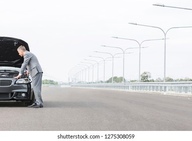 Business professional looking at breakdown car on road against sky