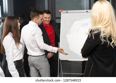 Business professionals. Group of young confident bisiness people analyzing data using office board while spending time in the office