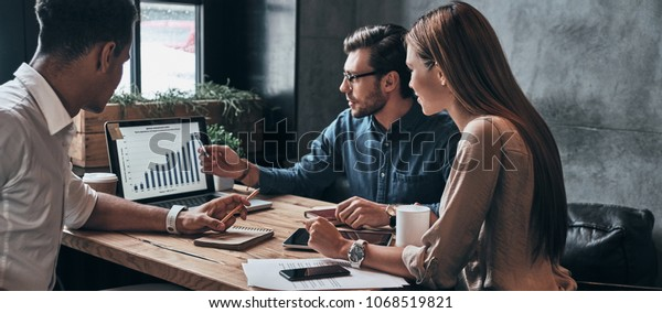 Business professionals. Group of young confident business people analyzing data using computer while spending time in the office