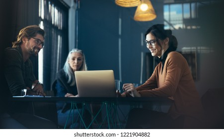 Business professionals sitting around table and looking at laptop. Asian female executive giving a presentation over laptop to colleagues at office.