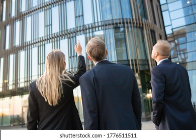 Business professionals in suits looking at office building facade, pointing up, discussing real property. Back view, low angle. Commercial real estate concept