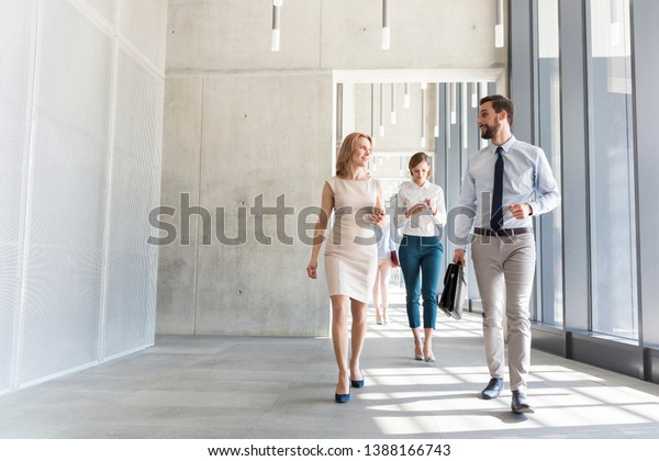 Business professionals talking while walking in office corridor