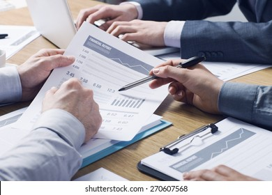 Business professionals working together at office desk, hands close up pointing out financial data on a report