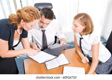 Business project concept. Red-haired lady showing several documents to the manager about business ideas and projects concerning their company they work for.