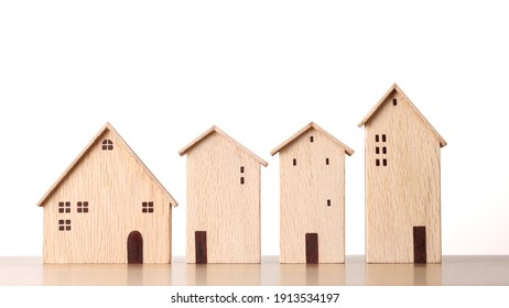 Business property investment concept, model wooden houses on wooden desk on white background studio for financial real estate advertising concept