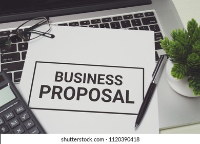 Business Proposal on white paper placed on top of laptop computer. Business concept.
