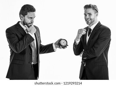 Business and punctuality concept. Businessmen misunderstanding about timing. Men in classic suits with opposite emotions stand on white background. Businessman holds clock with thoughtful face.