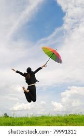 Business rainbow umbrella woman jumping to blue sky in grassland with rainbow umbrella