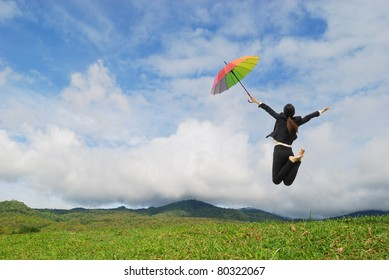 Business rainbow umbrella woman jumping to blue sky in grassland