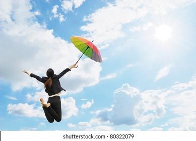Business rainbow umbrella woman jumping to blue sky