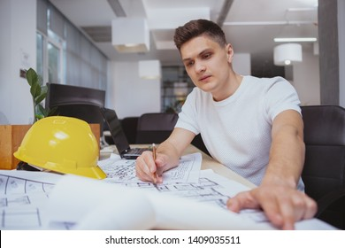 Business, real estate concept. Attractive young male engineer drawing building plan sketches at his office, examining blueprints