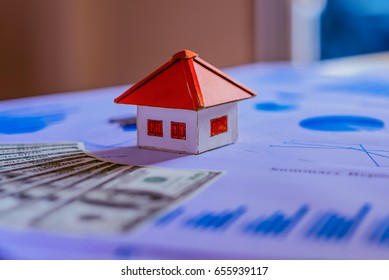 Business Real Estate Concept, House model with a key and dollar bills put on paper graph on wooden background.