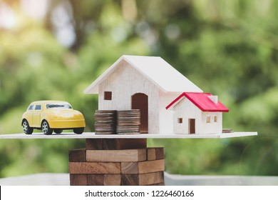 Business real estate investment concept : Wooden home, car with stack of money coins on wooden blocks scales in balance. Property mortgage, financial or insurance house, essentials for life ideas