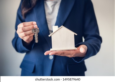Business Real Estate and Residential Investment Concept, Broker Sell Agency of Property Estates Giving Keys for New Housing to Customers While Holding House Model. Business Financial/Investing